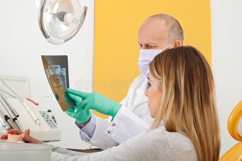 Zahnarzt und Patient, die zum zahnmedizinischen Röntgenstrahl schauen lizenzfreie stockfotos