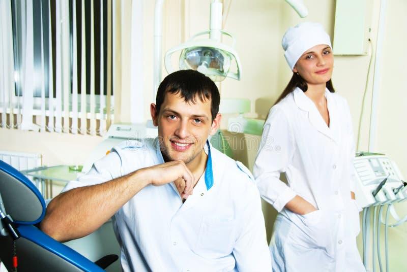 Zahnarzt und sein Assistent im Büro stockbilder