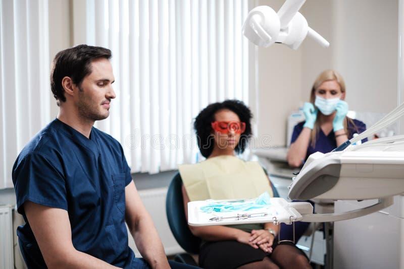 Zahnarzt und seine behilfliche Funktion in der Privatpraxis lizenzfreie stockfotografie
