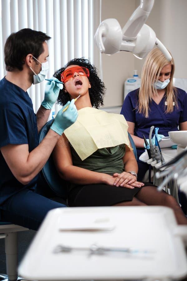 Zahnarzt und seine behilfliche Funktion in der Privatpraxis stockbilder