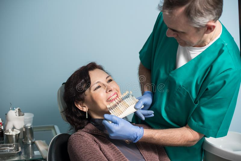Zahnarzt und weiblicher Patient, die Farbe der Zähne im zahnmedizinischen Klinikbüro überprüfen und vorwählen zahnheilkunde lizenzfreie stockfotos