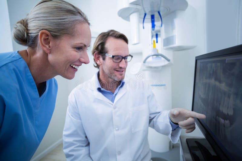 Zahnarzt und Zahnarzthelfer, die einen Röntgenstrahl auf dem Monitor besprechen lizenzfreies stockfoto