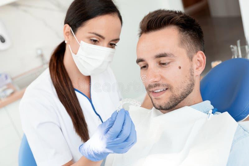 Zahnarzt zeigt unsichtbare Klammern Aligner lizenzfreie stockbilder