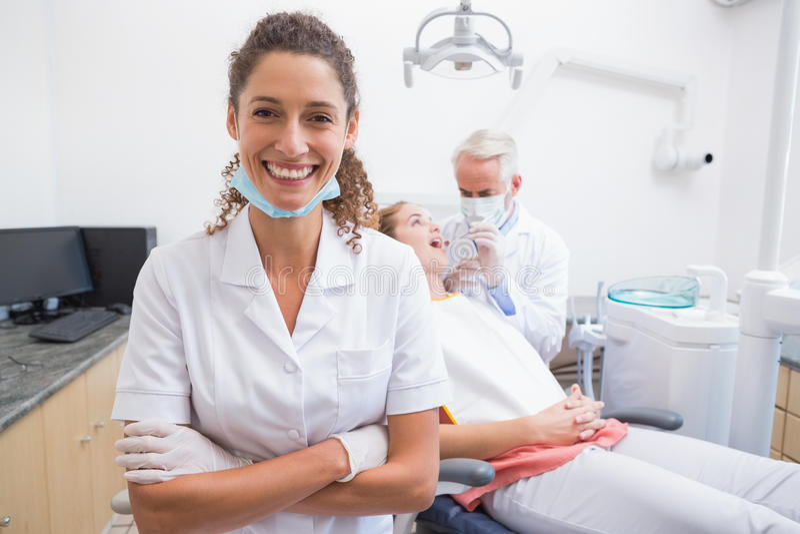 Zahnarzthelfer, der an der Kamera mit Zahnarzt und Patienten hinten lächelt lizenzfreie stockfotografie