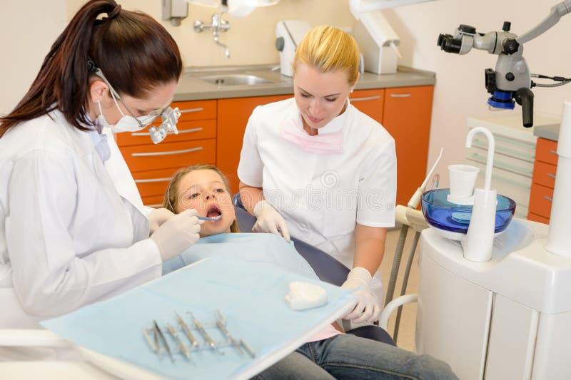 Zahnarzthelfer mit Zahnarzt und kleinem Kind lizenzfreie stockfotos