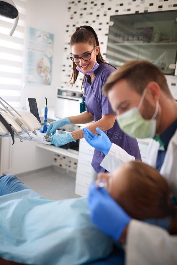 Zahnarzthelfer und Zahnarzt, die mit Patienten arbeitet stockbild