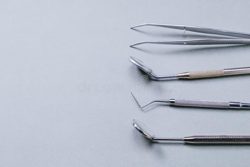 Zahnarztwerkzeuge: zwei Spiegel, zahnmedizinische Sonde und Pinzette auf grauem Hintergrund auf rechter Seite stockbild