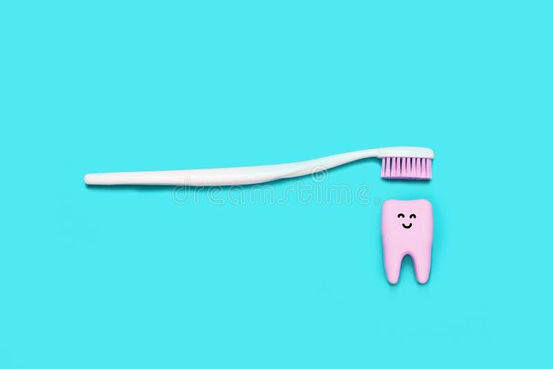 Zahnbürste und großer lächelnder Zahn auf blauem Hintergrund minimal lizenzfreie stockfotografie