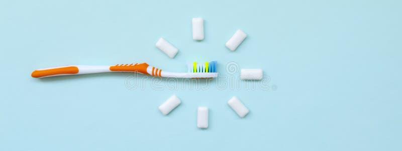 Zahnbürste und Kaugummis liegen auf einem blauen Pastellhintergrund Draufsicht, flache Lage Minimales Konzept stockfoto