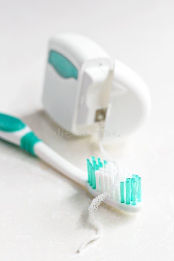 Zahnbürste und Zahnseide auf weißem Hintergrund stockfotografie