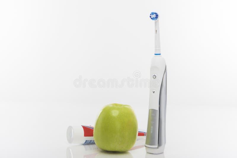 Zahngesundheits-Konzept: Grünes Apple, Zahnpasta mit elektrischem auch lizenzfreies stockbild