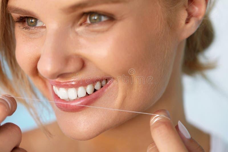 Zahnmedizinische Gesundheit Frau mit dem schönen Lächeln, das gesunde Zähne Flossing ist lizenzfreie stockbilder