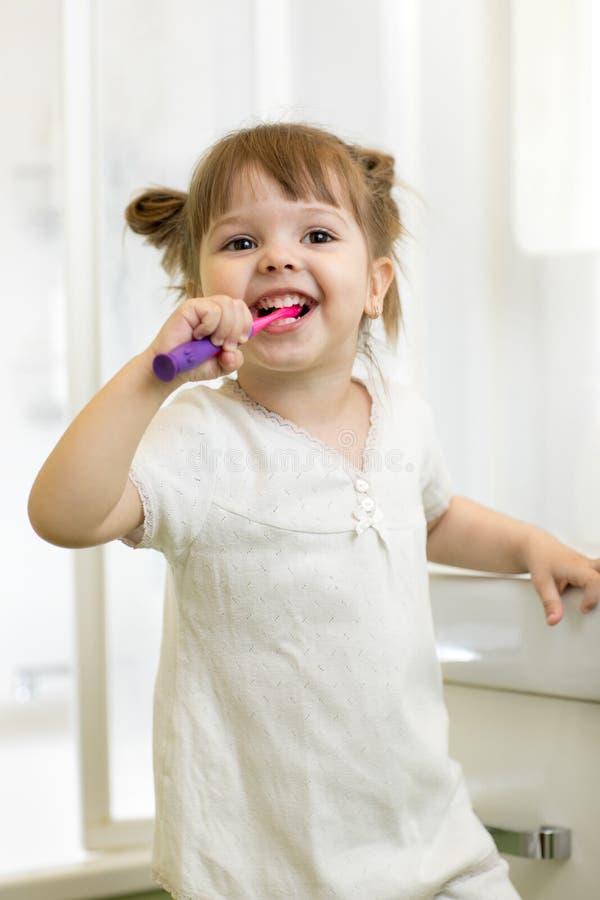 Zahnmedizinische Hygiene Lächelndes Kindermädchen, das ihre Zähne putzt lizenzfreies stockbild