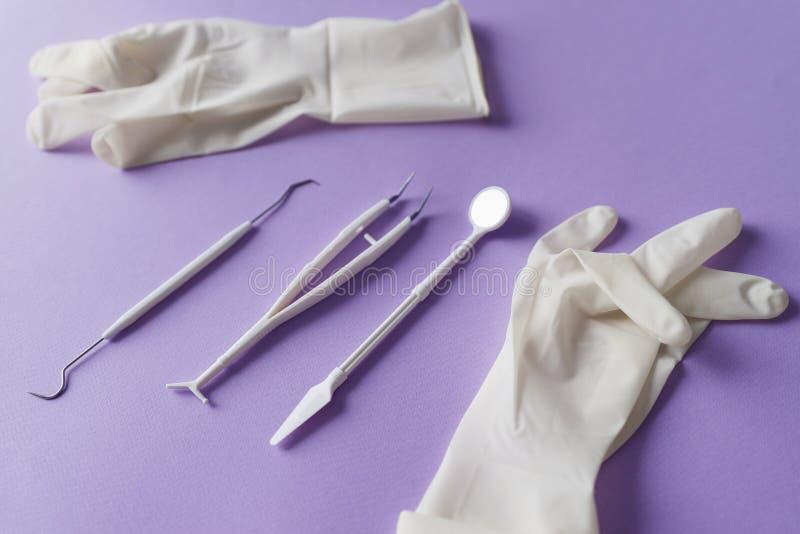 Zahnmedizinische Instrumente und medizinische Handschuhe auf buntem Hintergrund lizenzfreie stockfotos