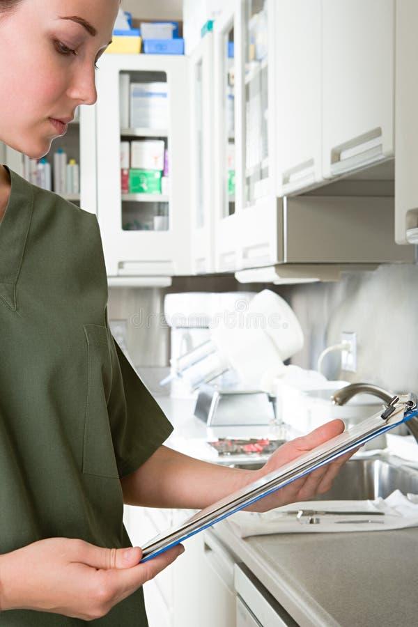 Zahnmedizinische Krankenschwesterlesung lizenzfreies stockfoto