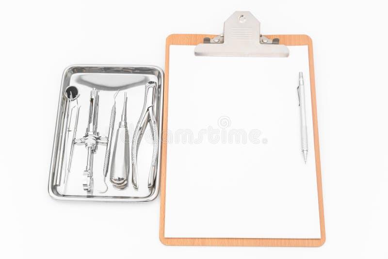 Zahnmedizinische Werkzeuge, Ausrüstung und zahnmedizinisches Diagramm auf weißem Hintergrund lizenzfreie stockfotografie
