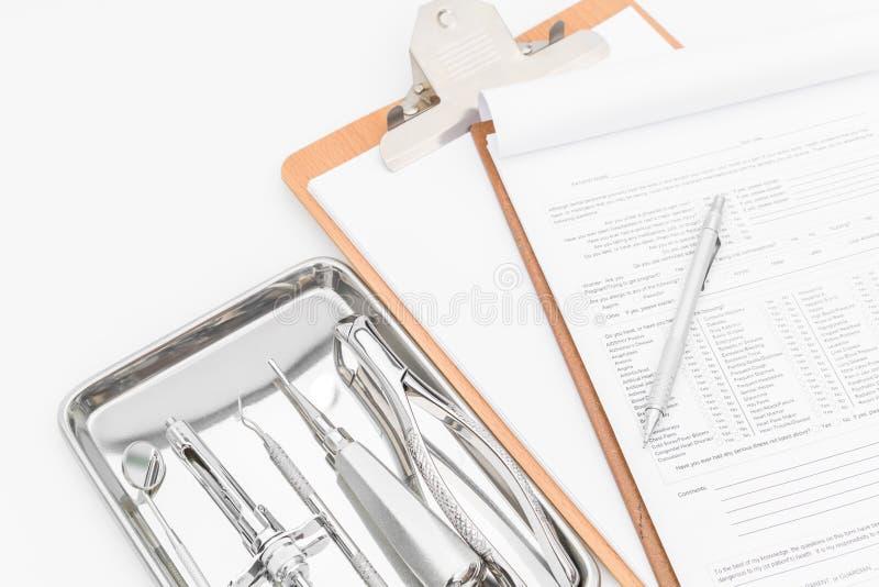 Zahnmedizinische Werkzeuge, Ausrüstung und zahnmedizinisches Diagramm auf weißem Hintergrund lizenzfreie stockbilder