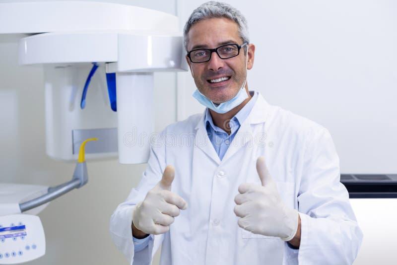 Zahnmedizinischer Zahnarzt, der sich Daumen zeigt lizenzfreie stockbilder