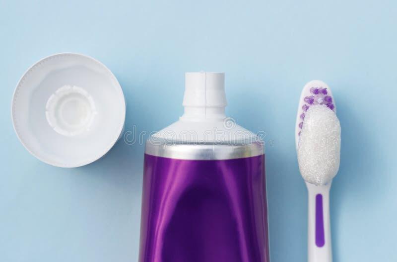 Zahnpasta im Rohr und in der Zahnbürste auf blauem Hintergrund Mundpflege-Konzept lizenzfreies stockfoto