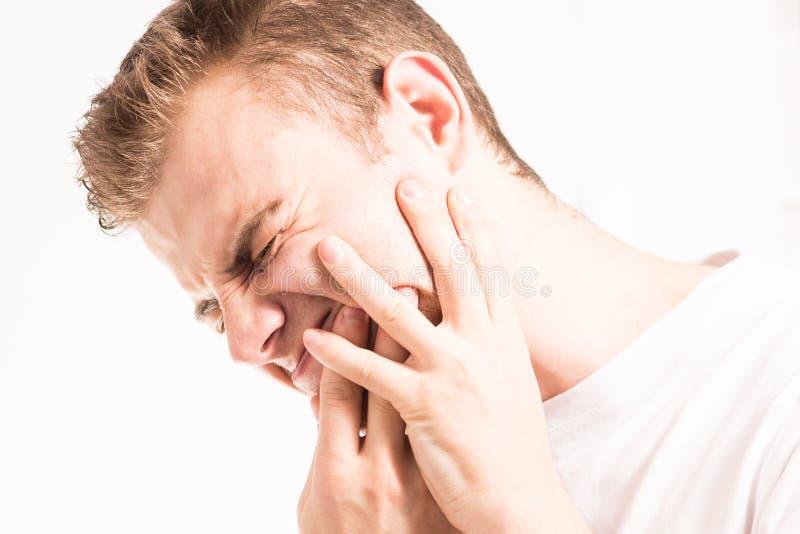 Zahnschmerzen, Medizin, Gesundheitswesenkonzept, Zahn-Problem, junger Mann, der unter den Zahnschmerz, Karies, in einem weißen T- stockfoto