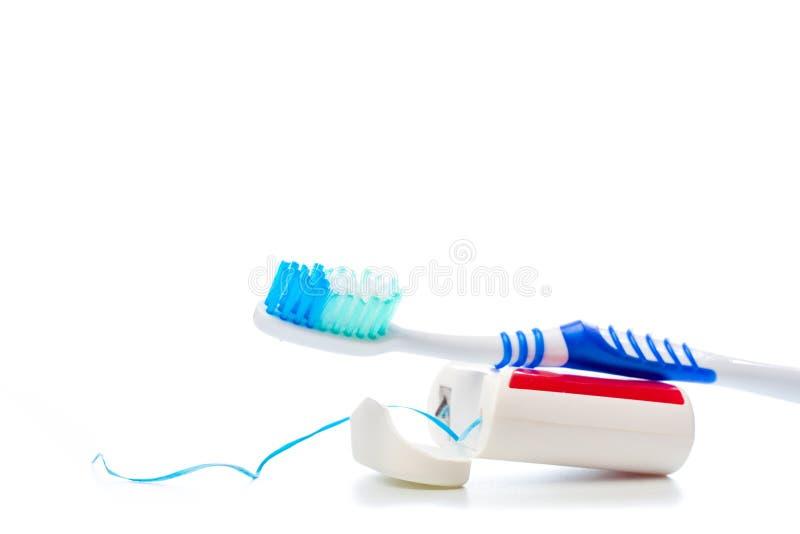 Zahnseide und Zahnbürste auf einem lokalisierten Hintergrund lizenzfreies stockbild