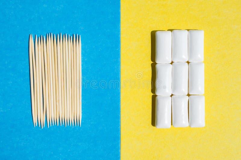 Zahnstocher auf blauen Hintergrund- und Gruppenkaugummis im weißen Behälter auf gelbem Hintergrund, Draufsicht stockfotografie