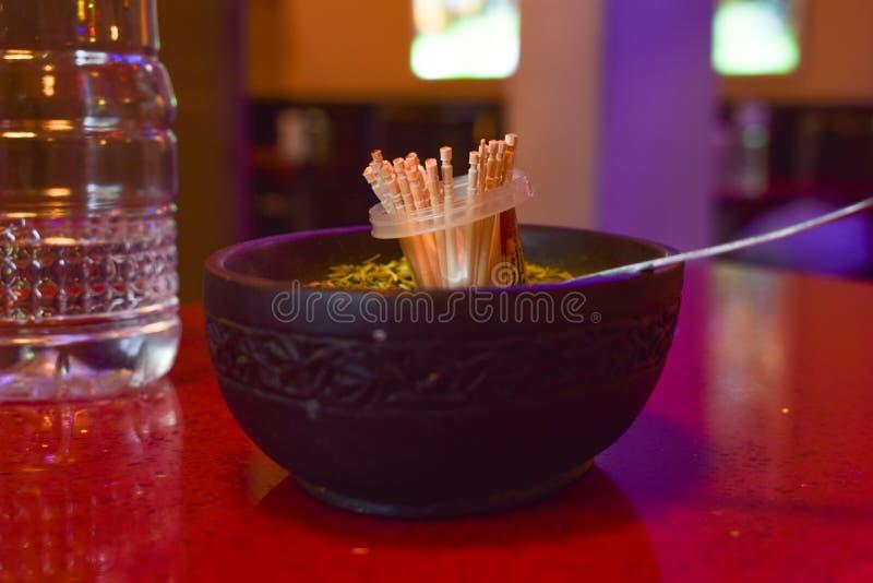 Zahnstocher auf einer Tabelle im Restaurant Löffel, Wasserflasche und andere Einzelteile auf einer Tabelle Bunter Hintergrund lizenzfreie stockfotografie