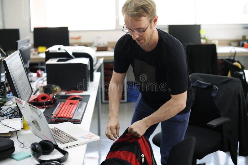 Zaino afferrante dell'uomo che va dopo l'ora del lavoro immagini stock libere da diritti