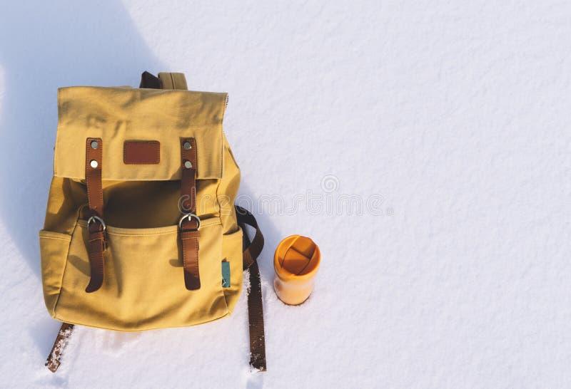 Zaino arancio con gli elementi di cuoio e termos giallo di tè o di caffè caldo su un fondo di neve pura bianca in supporto di inv fotografia stock