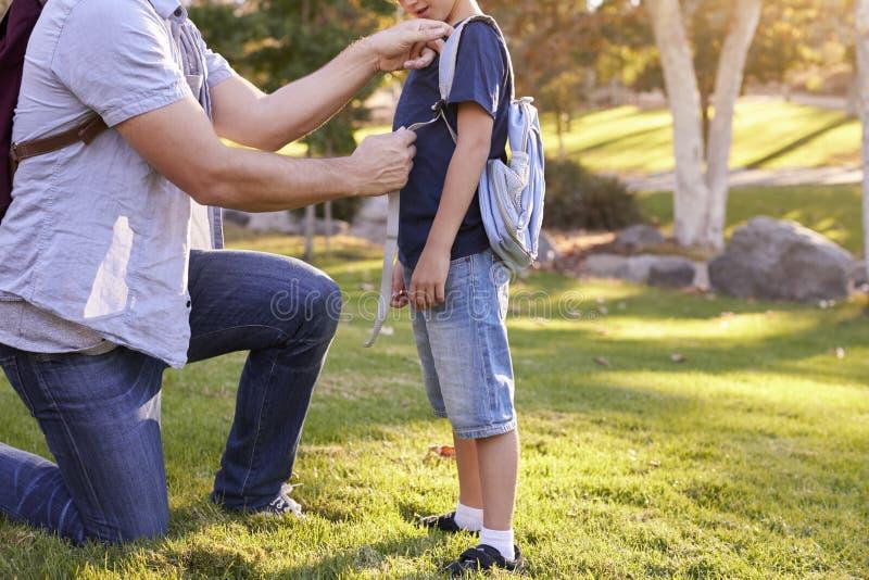 Zaino del ` s di Fastening Son del padre come si preparano per l'aumento fotografie stock libere da diritti