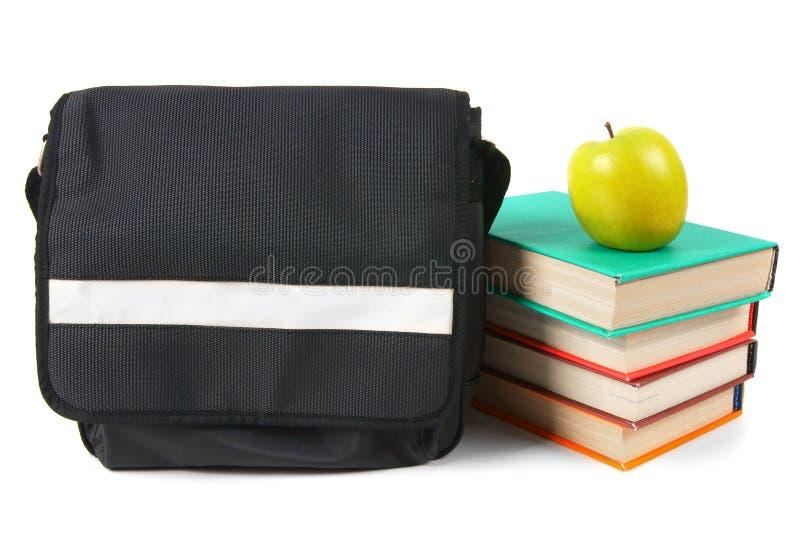 Zaino della scuola, libri e una mela immagini stock