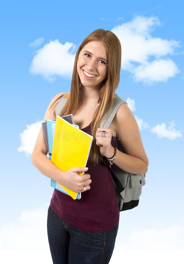 Zaino di trasporto e libri della giovane bella ragazza dello studente di college sotto cielo blu fotografia stock
