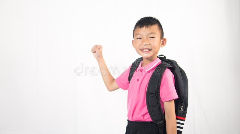 Zaino felice della tenuta dello studente del bambino su fondo bianco immagini stock libere da diritti