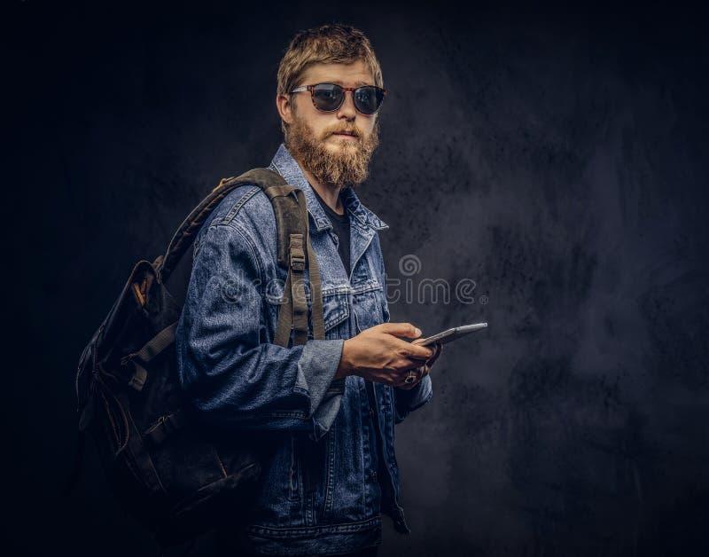 Zaino il tipo barbuto dei pantaloni a vita bassa che indossa gli occhiali da sole e vestiti in rivestimento dei jeans tiene un co fotografie stock libere da diritti