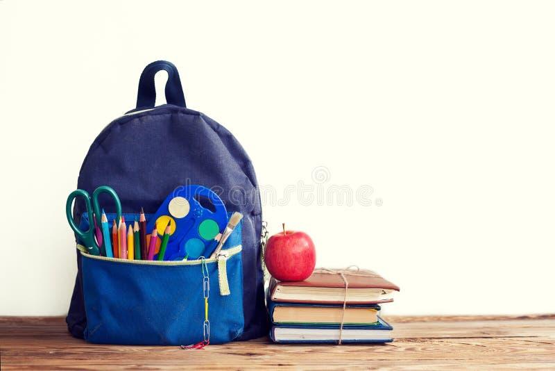 Zaino pieno della scuola con i libri e mela su fondo bianco immagine stock libera da diritti