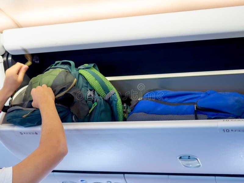 Zaino verde mettente della mano sull'armadio dell'aeroplano fotografia stock libera da diritti