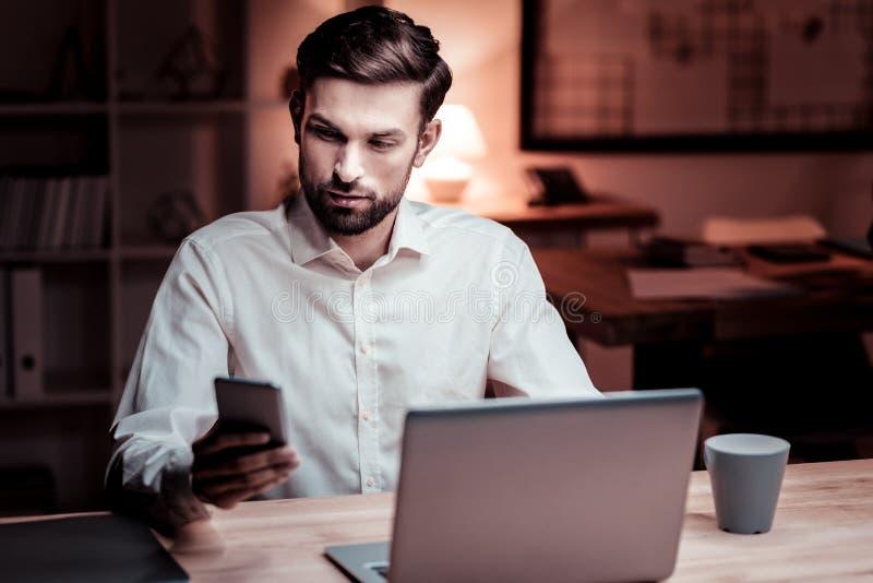 Zainteresowany przystojny pracownik jest usytuowanym jego telefon komórkowego i używa zdjęcie royalty free