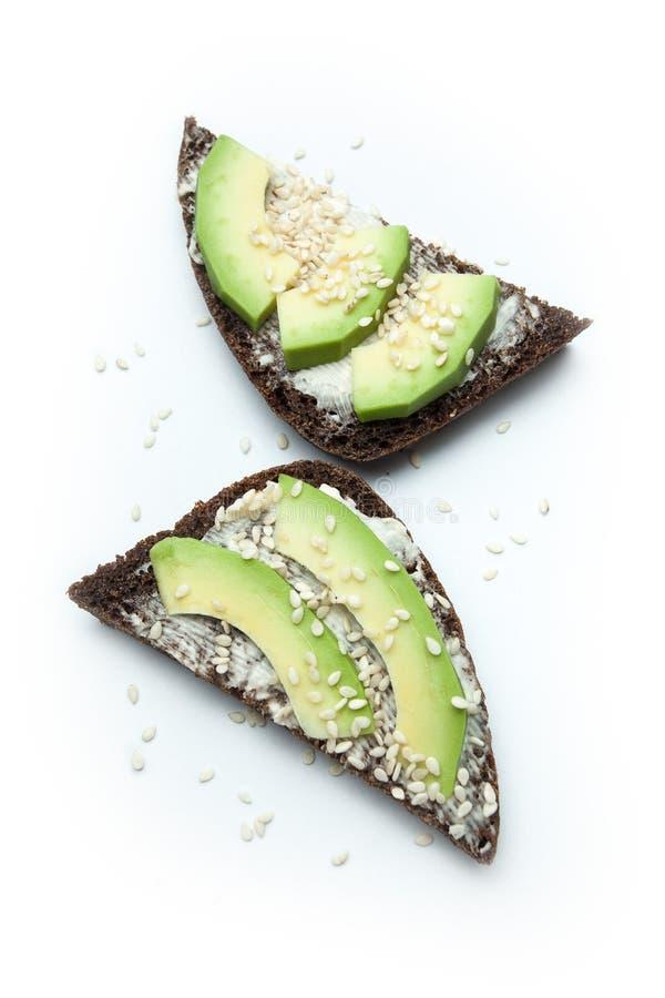 Zakąska od avocado na czarnym chlebie i sezamowych ziarnach odosobnionych na białym tle, fotografia stock