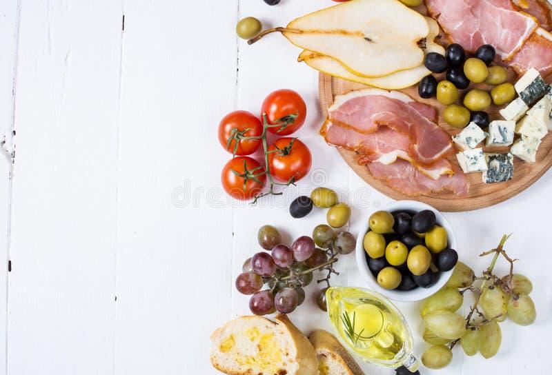 Zakąska, włoski antipasto, baleron, oliwki, ser, chleb, winogrona, bonkreta na białym drewnianym tle obrazy royalty free