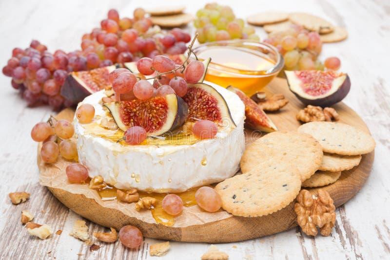 Zakąski camembert, miód, dokrętki, owoc i krakers -, obraz stock