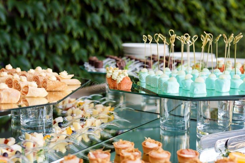 Zakąski, palcowy jedzenie, partyjny jedzenie, suwaki Canape, tapas cukierniany słuzyć lato stołu taras Catering usługa zdjęcia royalty free