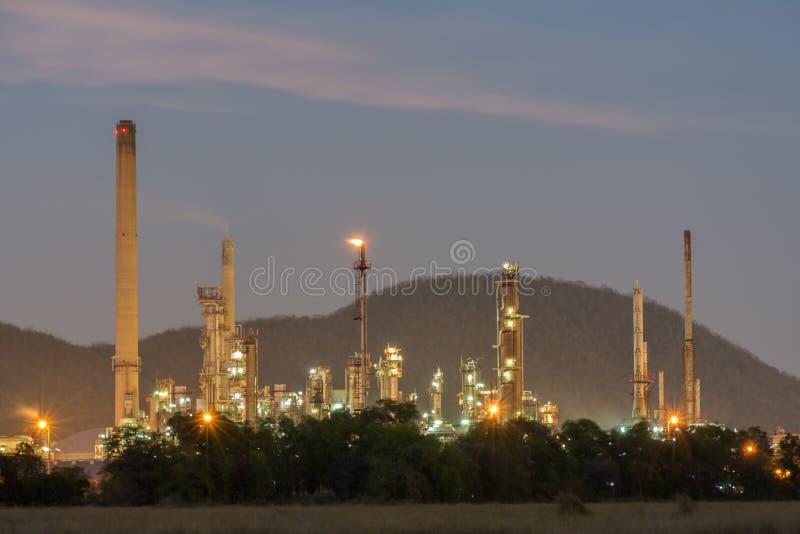 Zakład petrochemiczny za krzakiem podczas mrocznego czasu zdjęcia stock