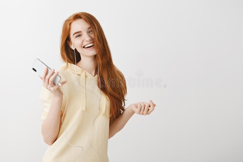 Zakłada ścieżkę dźwiękowa jej nastrój Portret pozytywna atrakcyjna dziewczyna z imbirowym włosianym tanem, mienia smartphone fotografia royalty free