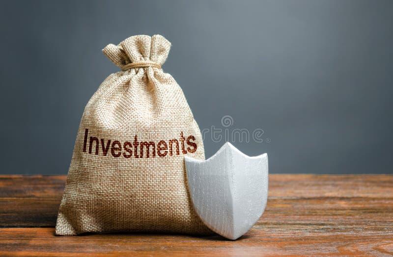 Zak met de het inschrijvingsinvestering en schild Waarborg van bescherming van buitenlandse investering in de economie stock afbeeldingen