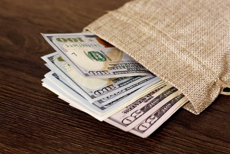 Zak met geld, dollars Dollars op een donkere houten background_ royalty-vrije stock afbeeldingen