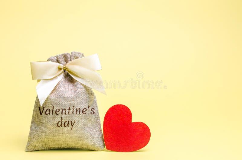 Zak met geld en rood hart met de Dag van woordvalentine Het geld van de besparing accumulatie Het kopen van giften aan uw gehoude stock foto