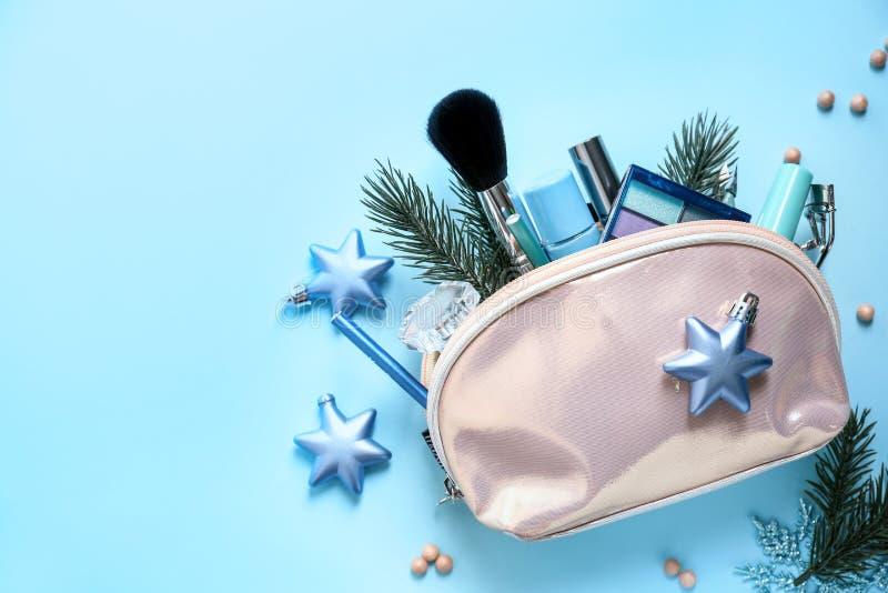 Zak met schoonheidsmiddelen en Kerstmisdecoratie op kleurenachtergrond royalty-vrije stock foto's