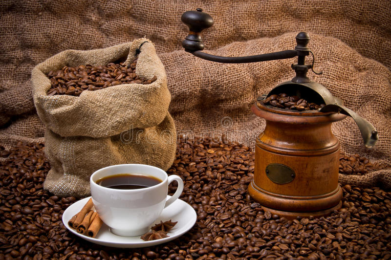 Zak van koffiebonen, witte kop en koffiemolen stock afbeelding