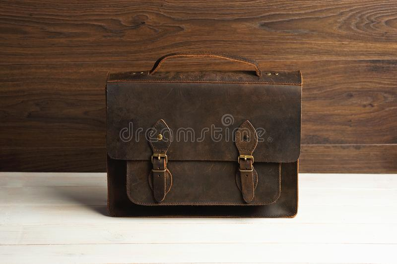 Zakaktentas voor zakenmanmensen, leer bruine zak op een houten achtergrond Mensen` s manier, toebehoren, bedrijfsachtergrond stock foto's