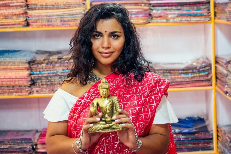 Zakelijke dame indiaanse verkoper traditie rode sari souvenir shop buddha shiva figurine yoga meditatie meisje in india in de sta stock foto's